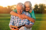 Senior couple reading book. Stock Photos