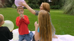 A mother rubs a ballon on her son's head to create static electricity - handheld Stock Footage