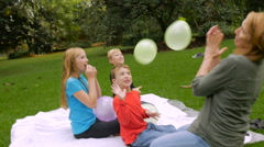 Three children and a mother letting balloons fly away - slomo handheld Stock Footage