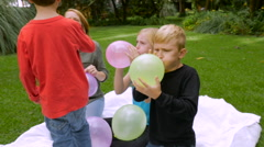 A mother and her three children blow up balloons together - slowmo Stock Footage