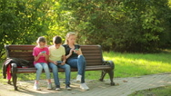 Mother with children sitting on the bench and use mobile smartphones Stock Footage