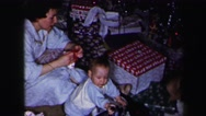 1972: family on the floor opening christmas gifts under the tree LYNBROOK Stock Footage