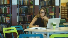 Girl student working at a computer in the library along with books Stock Footage