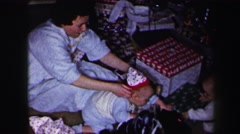 1972: parents putting matching stocking caps on kids xmas tree patterned Stock Footage