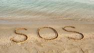 The inscription SOS on sand Stock Footage