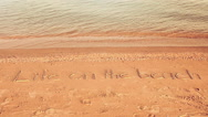 Life on the beach concept - inscription on a beach sand with coming wave Stock Footage