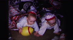 1972: twin baby brothers dressed identically xmas tree crawling LYNBROOK Stock Footage