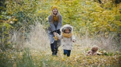 Mother and her daughter little girl walking in a autumn park - child running Stock Footage