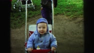 1972: bouncy baby rides in stroller on grassy ground LYNBROOK, NEW YORK Stock Footage