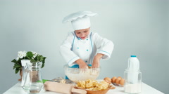 Young baker girl playing with dough and laughing at camera. Hands in dough Stock Footage