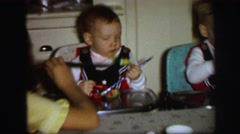1972: high chair babies at their birthday party with mom off to the side Stock Footage