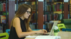 Beautiful female student working with laptop in the city library Stock Footage