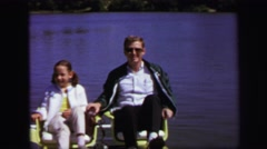 1972: young girl and man paddle across lake. LYNBROOK, NEW YORK Stock Footage