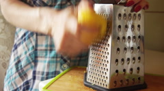 A woman in a plaid shirt rubbing lemon zest for cooking baking Stock Footage