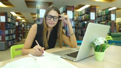 Female student taking notes from book Stock Footage