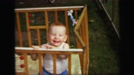 1972: baby playing in wood crib happy redhead caucasian child LYNBROOK, NEW YORK Stock Footage