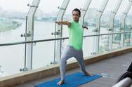 Serious young sporty man doing yoga on balcony Stock Photos