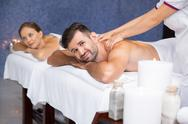 Smiling man having massage and woman in spa center Stock Photos