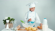 Young baker break an egg and adds it in the dough Stock Footage