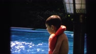 1972: kid wearing lifejacket swimming poolside LYNBROOK, NEW YORK Stock Footage