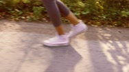Close-up of female legs running gently on paved road Stock Footage