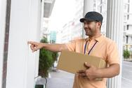Young man making home delivery Stock Photos