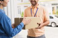 Courier making delivery to beautiful woman Stock Photos