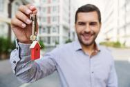 Smiling man holding up keys Stock Photos