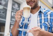 Handsome man relaxing with cup of latte Stock Photos