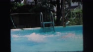 1972: young girl in bathing suit jumping into an above ground swimming pool. Stock Footage