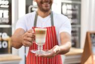 Smiling waiter standing in entrance of coffee shop Stock Photos