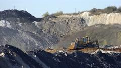 URGUN, RUSSIA - SEPTEMBER 26, 2016: Buldozer shoveling soil on open coal quar Stock Footage