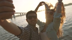 Happy couple in love taking selfie photo standing in front of a bright river Stock Footage