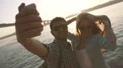 Two young people in love having fun on the river bank Stock Footage