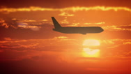 Plane flying in orange sky Stock Footage