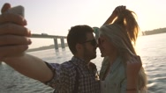 Kissing young couple takes photograph against brightly shining sun Stock Footage
