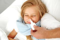 Hand with nose spray near sick child Stock Photos