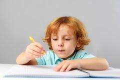 Intelligent kid drawing at lesson Stock Photos