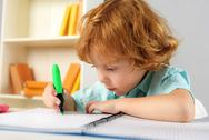 Concentrated pupil sitting with marker Stock Photos