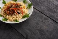 Noodles on a plate on a wooden table Stock Photos