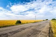 Countryside road among fields. Beautiful cloudy sky Stock Photos