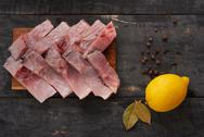 Pieces of fish on board and lemon Stock Photos