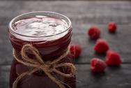 Raspberry jam and berries on a wooden table Stock Photos