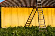Cute yellow rural house with wooden stairs in countryside Stock Photos
