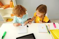 Intelligent children drawing in notebook indoors Stock Photos