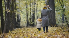 Mother and her daughter little girl playing in a autumn park - mommy and child Stock Footage