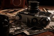 Old black and white photos and vintage camera on the table Stock Photos