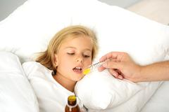 Sick child taking medicine Stock Photos
