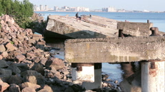 Huge Dilapidated Waterlogged Concrete Blocks with Resting People Stock Footage