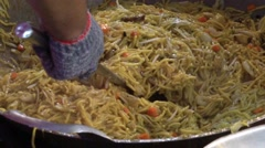 Yellow noodle being fried in hot pan ready to serve Stock Footage